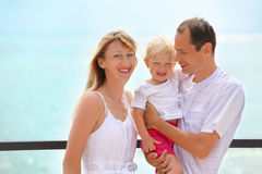 Gelukkige familie met meisje op veranda dichtbij zeekust stock foto's