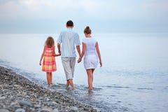 Gelukkige familie met meisjesgang op strand in avond Royalty-vrije Stock Afbeeldingen
