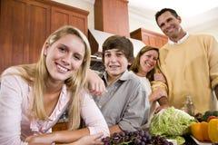 Gelukkige familie met tienerkinderen in keuken royalty-vrije stock foto's