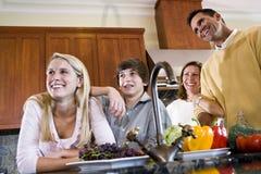 Gelukkige familie met tieners die in keuken glimlachen stock afbeelding