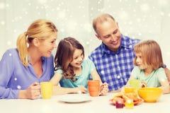 Gelukkige familie met twee jonge geitjes die ontbijt hebben royalty-vrije stock foto's