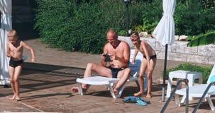 Gelukkige familie met twee jonge geitjes die pret in het zwembad hebben stock video