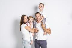 Gelukkige familie met twee jonge geitjes op studio grijze achtergrond royalty-vrije stock foto's