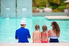 Gelukkige familie met twee jonge geitjes in openlucht zwembad Royalty-vrije Stock Fotografie