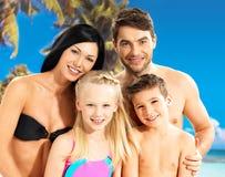 Gelukkige familie met twee kinderen bij tropisch strand Stock Afbeeldingen