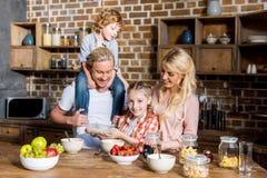 gelukkige familie met twee kinderen die en ontbijt samen voorbereiden eten stock afbeelding