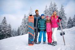Gelukkige familie met twee kinderen op de wintervakantie in berg stock fotografie