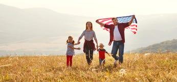 Gelukkige familie met vlag van Amerika de V.S. bij zonsondergang in openlucht royalty-vrije stock foto's