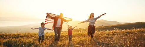 Gelukkige familie met vlag van Amerika de V.S. bij zonsondergang in openlucht Royalty-vrije Stock Afbeeldingen