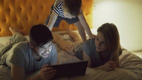 Gelukkige familie met weinig zoon die in bed thuis en het surfen sociale media op tabletcomputer vóór slaap liggen stock fotografie