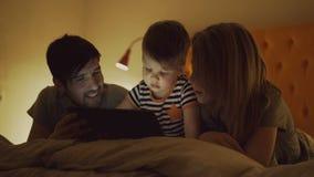 Gelukkige familie met weinig zoon die leren tabletcomputer te spelen die in bed thuis in avond liggen stock videobeelden