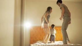 Gelukkige familie met weinig zoon die op bed thuis in de avond vóór slaap dansen stock video
