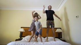 Gelukkige familie met weinig zoon die op bed thuis springen stock footage