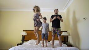 Gelukkige familie met weinig zoon die op bed thuis springen stock videobeelden
