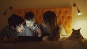 Gelukkige familie met weinig zoon en grappige kat die in bed liggen thuis en tabletcomputer voor het letten van beeldverhaal op f stock video