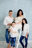 Gelukkige familie met zwangere vrouw en kinderen die in de studio stellen stock foto