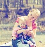 Gelukkige familie. moeder en baby voor een gang in het park voor aard Stock Afbeelding