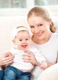 Gelukkige familie. Moeder en babydochter thuis op de bank Stock Fotografie