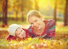 Gelukkige familie: moeder en kind weinig dochter die en in de herfst spelen lachen Stock Afbeeldingen