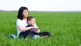 Gelukkige familie: moeder en kindzitting op het groene gras Het mamma en de jongen trekken met een tablet Technologie, toepassing stock videobeelden