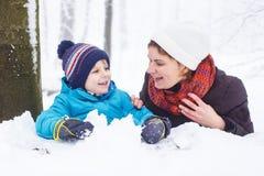 Gelukkige familie: moeder en weinig zoon die pret met sneeuw in wint hebben Stock Afbeeldingen