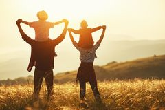 Gelukkige familie: moeder, vader, kinderenzoon en dochter op zonsondergang stock foto