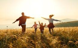 Gelukkige familie: moeder, vader, kinderenzoon en dochter op zonsondergang stock afbeeldingen