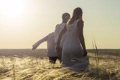 Gelukkige familie in nationale Slavische kleren die op gebied op zonsondergang lopen en handen houden Onthaal aan Rusland stock afbeelding