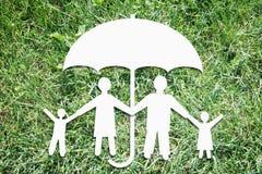 Gelukkige familie onder bescherming op achtergrond van groen gras Stock Afbeelding