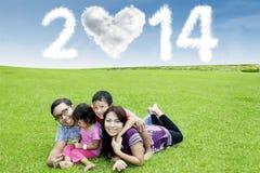 Gelukkige familie onder wolk van nieuw jaar 2014 Stock Foto's