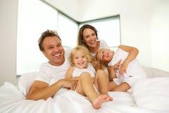 Gelukkige familie op bed in de slaapkamer Stock Foto