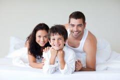 Gelukkige familie op bed met omhoog duimen royalty-vrije stock afbeeldingen