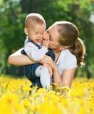 Gelukkige familie op een gang. moeder kussende baby Stock Afbeelding