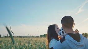 Gelukkige familie op een gebied van tarwe onder groene aartjes in de zon Samen omhelzen zij een kleine dochter Mooi stock footage