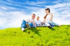Gelukkige familie op gras Royalty-vrije Stock Afbeeldingen