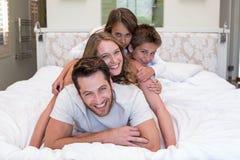 Gelukkige familie op het bed stock afbeelding