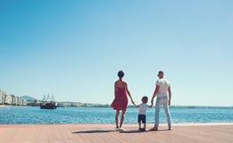 Gelukkige Familie op het Strand De mensen bekijken toekomst op de zomervakantie Vader, moeder en kind tegen blauwe overzees en he stock foto