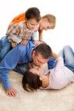 Gelukkige familie op het tapijt Stock Fotografie
