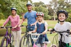Gelukkige familie op hun fiets bij het park Royalty-vrije Stock Foto's