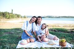 Gelukkige familie op picknick dichtbij het meer royalty-vrije stock afbeelding