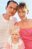 Gelukkige familie op strand dat, vast eruit ziet Stock Afbeeldingen