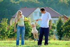 Gelukkige familie op weide Stock Afbeeldingen