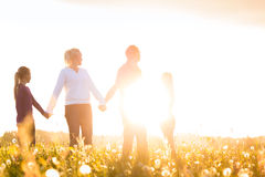 Gelukkige familie op weide bij zonsondergang Stock Afbeelding