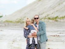 Gelukkige familie in openlucht De ouders houden de zoon op handen stock fotografie