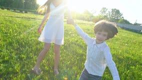 Gelukkige familie in openlucht moeder en zoon weinig jongen die genietend de aard van zomer bij zondag lopen moeder en kind, leuk stock video