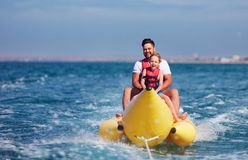 Gelukkige familie, opgetogen vader en zoon die pret hebben, die op banaanboot tijdens de zomervakantie berijden stock fotografie