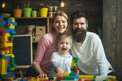 Gelukkige familie Opgewekte jong geitjezitting tussen glimlachende ouders Mamma en papa die terwijl jong geitjespelen met lachen royalty-vrije stock afbeeldingen