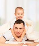 Gelukkige familie. Papa en zoons het spelen in bed Stock Afbeelding