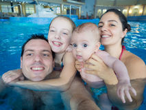 Gelukkige familie in pool stock fotografie
