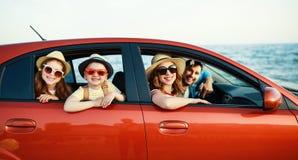 Gelukkige familie in reis van de de zomer de autoreis door auto op strand stock foto's